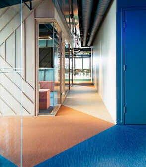 藍色橘粉色米色大塊現場切割拼花而成的bolon PVC編織地板鋪在活潑簡約風格的辦公室設計空間