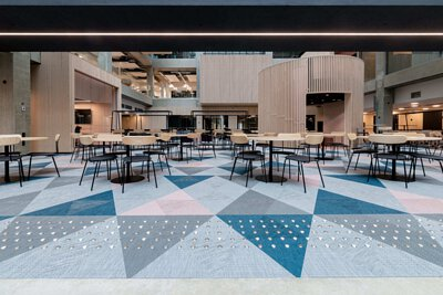 芬蘭學校educity中庭鋪設三角形藍色、粉色、灰色的瑞典Bolon編織地板