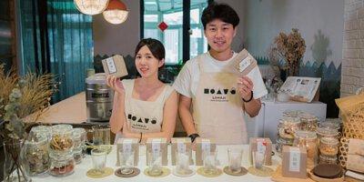 樂木集創辦人Hung與April拿著產品,桌上擺有樂木集的漢方茶與玻璃杯