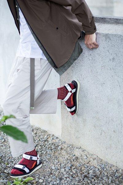 """機能襪履設計品牌 nozzle quiz 經典""""STREET AGILITY"""" 系列 lookbook,suicoke的白色涼鞋有著絕佳的百搭特性,紅色編織長襪顯示出你不安分的穿著玩心。"""