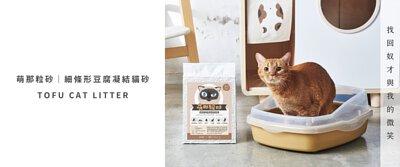 貓咪蹲在貓砂盆,旁邊有一包貓砂