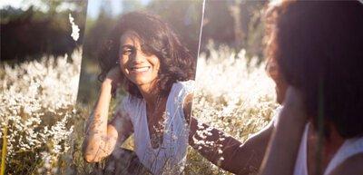 一個女人在花叢中對著鏡中的自己微笑