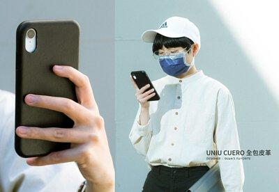 一個戴口罩的人拿著 IPHONE XR 手機