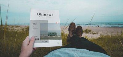 一個人海邊躺在綠油油的草地上,看著雜誌本回憶過往的旅程