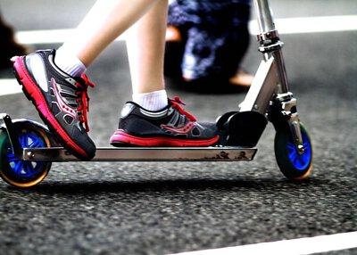 一個人穿著紅色的鞋子騎著鋁合金的電動滑板車