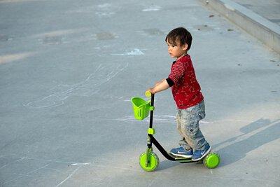 騎著綠色附有籃子的電動滑板車的小男孩