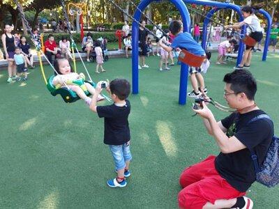 拿兒童相機的男孩與攝影的爸爸