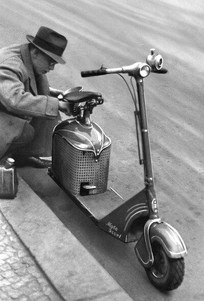 一名年輕人正在用漏斗給他的Autoped踏板車加油