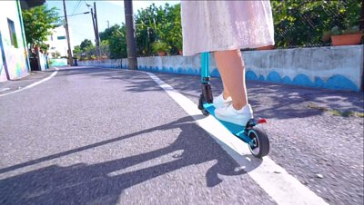 一個女孩騎著藍色的X5鋁合金電動滑板車在路上騎乘