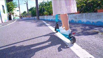 一個女生在路上騎電動滑板車