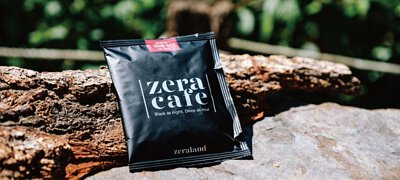 一包ZeraCafe單品濾掛咖啡放在戶外石頭上,倚靠著一塊原木