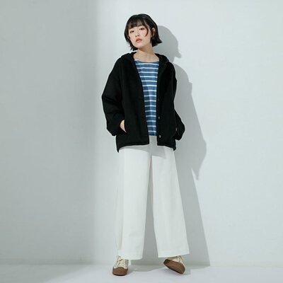 女模特兒身穿黑色連帽羊毛毛呢外套和白色打折造型長褲