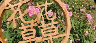 在玫瑰花叢前,有圓形木製招牌,招牌是鏤空的,品牌名稱是「花花草草」