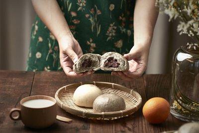 桌面上的竹籃裡放著兩個包子,一位女性站在桌子後方,雙手正剝開一只紅豆包。