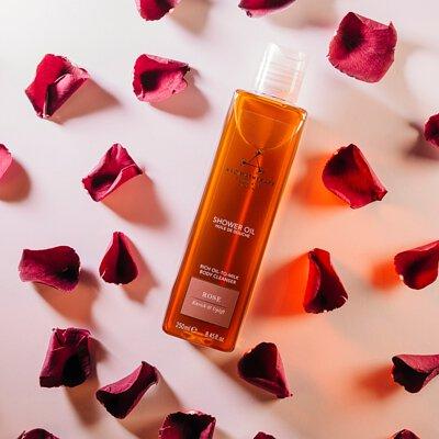 佈滿桃紅色玫瑰花瓣,彼此間有一點空隙,花瓣中間躺放一個透明長方形的罐子,裡面裝有琥珀色液體