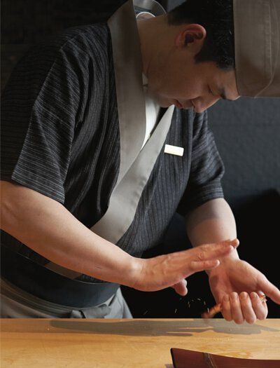 sushi chef, concentrated, was in preparation of the delectable nigiri sushi